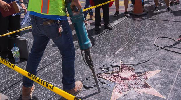 A worker removes the remains of the Star of US President Donald Trump on the Hollywood Walk of Fame after it was destroyed by a vandal