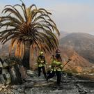 Firefighters walk among the ashes of a wildfire-ravaged home