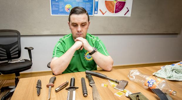 Eddie Burns with some of the weapons handed in to St Malachy's youth club