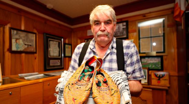 Kevin Carson, the curator of the Roddy McCorley Society living history museum in Belfast, holds a pair of Colonel Gaddafi's slippers