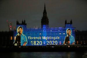 An image of Florence Nightingale is projected on the Houses of Parliament