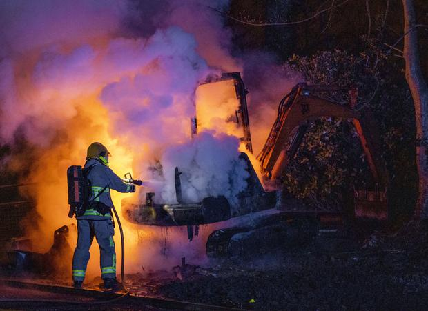 A member of the Northern Ireland Fire and Rescue Service extinguishes a digger which was set alight close to the loyalist Nelson Drive Estate in Londonderry (Liam McBurney/PA)