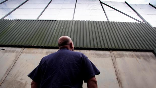 A man looks up at one of Belfast's peace walls
