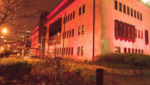 Derry City and Strabane District Council building lit up in red, in memory of Ryan McBride and the victims of the Buncrana pier tragedy