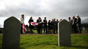 A Polish delegation gathers to pay tributes at the graves of seven Polish airmen killed during the Second World War, at Milltown Cemetery, West Belfast