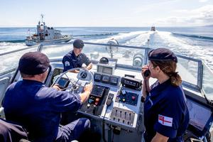 Lt Rebecca Anderson (right) aboard HMS Biter with chief petty officer Graeme Hinton at the helm and able seaman Ryan Dargue during manoeuvres on the north Antrim coast