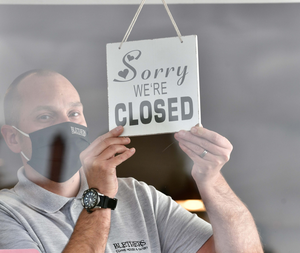 Shutdown: Gary Monteith puts up a 'closed' sign at Blethers Cafe on the Cregagh Road in east Belfast