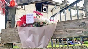 Flowers left at the fire-damaged home