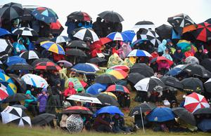 Fans shelter from the wind and rain