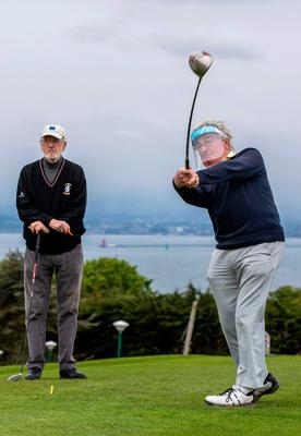 Liam Cahill looks on as Michael O'Hanlon, wearing a protective visor, plays at Howth Golf Club in Dublin