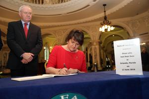 First and Deputy First Ministers Arlene Foster and Martin McGuinness sign a book of condolence at Belfast City Hall