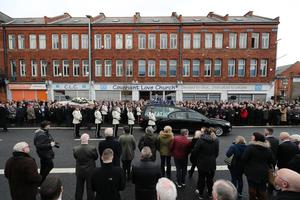 Mourners look on as Ian Ogle's coffin is carried to the Covenant Love Church (Niall Carson/PA)