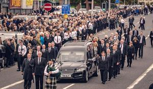 Crowds: The funeral procession makes its way through Andersonstown, west Belfast, in June