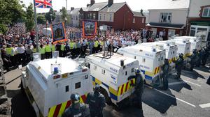 PSNI officers stop Orangemen and loyalists from marching along the Woodvale Road in Belfast during last year's Twelfth celebrations