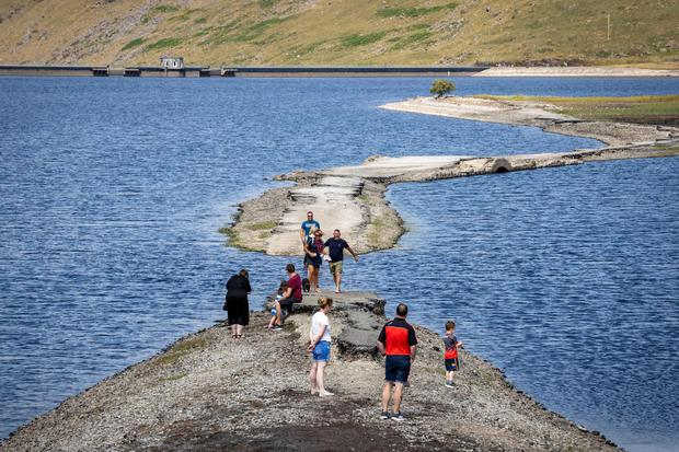 People walk along a pathway exposed by the falling water level at Spelga Reservoir in the Mourne Mountains of County Down. Pic: Liam McBurney/PA Wire