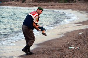 A paramilitary police officer carries the lifeless body of Aylan Kurdi, 3, after a number of migrants died and a smaller number were reported missing after boats carrying them to the Greek island of Kos capsized