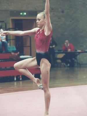 A young Debbie competing as a Commonwealth gymnast