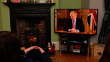 Members of a family listen as Prime Minister Boris Johnson makes a televised address from inside 10 Downing Street last night