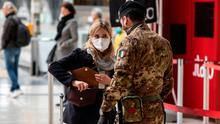 An Italian soldier speaks to a passenger at Milano Centrale train station