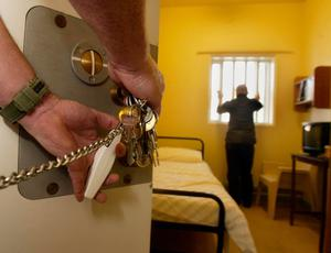 Vaccine call: A prison officer opens door of a cell