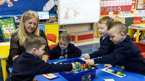 Teacher Joanne Conlon with some of her class pupils on their first day in P1 at St John the Baptist Primary School in west Belfast, as almost all schools have reopened and over 300,000 pupils have returned to school in Northern Ireland for the first time since mid-March.