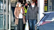 Cover up: Shoppers wearing masks leave Sainsbury's at Holywood Exchange near Belfast yesterday