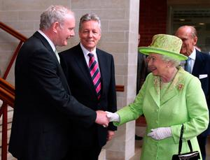 The Queen shakes hands with Martin McGuinness as Peter Robinson looks on at the Lyric Theatre, Belfast, in 2012