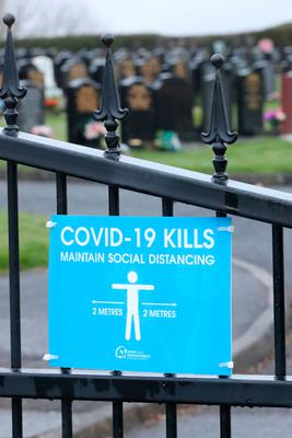 A Covid-19 sign on the entrance gates of Belmont cemetery in Antrim