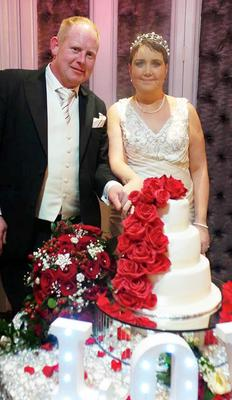 Lisa and Noel Watt cutting the cake at their wedding last month