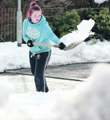 26.03.13. PICTURE BY DAVID FITZGERALD  The snow has forced people into abandoning cars and clearing the roads and their driveways as it has not thawed. Windermere Park in Four Winds, Belfast. Leeanne Fairfield helping to clear the road