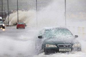Drivers negotiate the seafront road as waves breach the sea wall in the coastal village of Carnlough