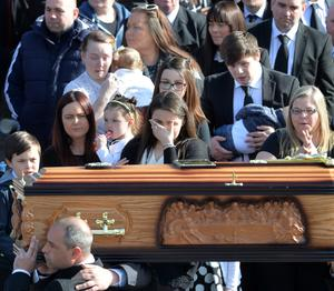 Michael McGibbon's family and friends watch as his coffin is carried into the church