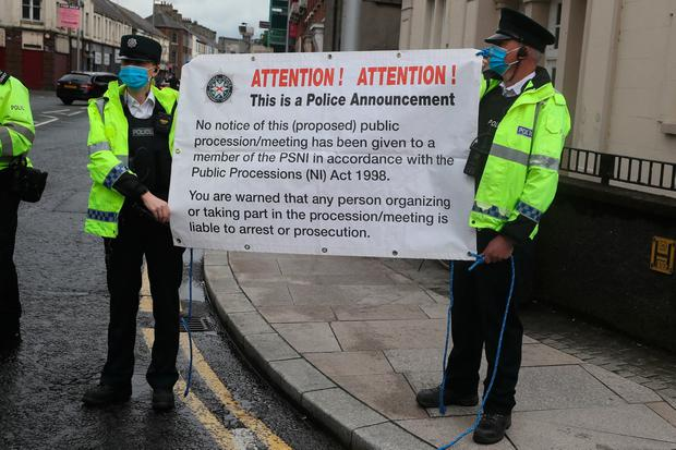 Police officers hold up a sign as loyalists take part in a rally against the Northern Ireland Protocol in Portadown.  Brian Lawless / PA Wire.
