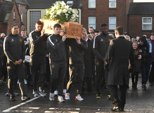 Team mates from Carrick carry Gerard's coffin during his funeral