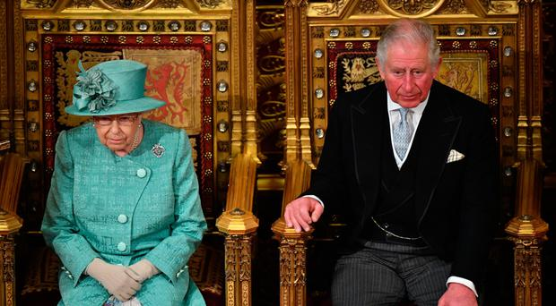 Queen Elizabeth II delivers the Queen's Speech alongside Prince Charles in the House of Lords Chamber yesterday
