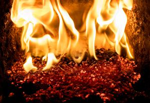 Pellets burning inside a biomass boiler on the farm of a poultry farmer