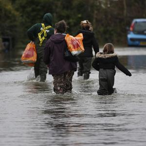 Members of the Bill family, carrying groceries, return to their house through the flooded part of the town of Staines