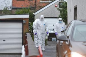 PSNI and forensic officers return to the scene of Eddie Girvan's murder at his home in Greenisland yesterday