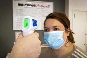 Paige Hegarty (right) has her temperature checked at Hollywood Nail Salon in Belfast by nail manicurist Rebecca Clarke, as lockdown restrictions ease allowing nail salons to reopen. PA Photo. Picture date: Monday July 06, 2020. See PA story ULSTER Coronavirus. Photo credit should read: Liam McBurney/PA Wire