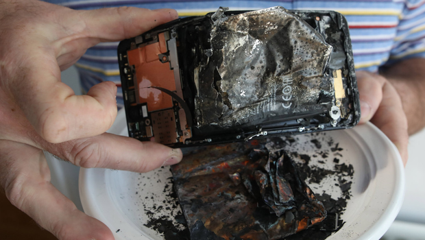 Paul Stewart holds the remains of his son's phone after it caught fire