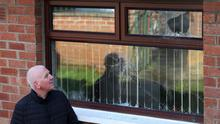 Martin Finucane beside the window damaged in the bomb attack