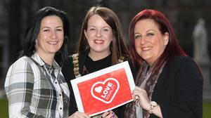 Same sex couple Amanda McGurk and Cara McCann pose for pictures with Lord Mayor Nuala McAllister outside Belfast City Hall (Niall Carson/PA)