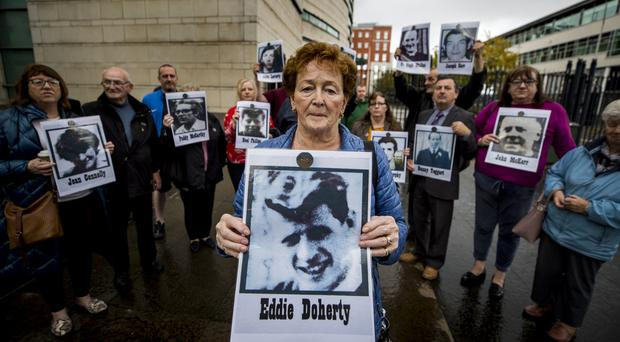 Kathleen McCarry holds an image of her brother Eddie Doherty, who died during the disputed series of shootings in a Ballymurphy area of Belfast in August 1971 which is the subject of fresh inquests at Belfast Coroner's Court (Liam McBurney/PA)