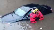 Firefighters rescue a person from a car in a flooded street in Blackpool