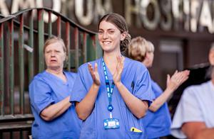 A nurse takes part in the salute to carers outside the Mater Hospital last night