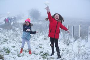 Having a ball: Youngsters enjoy the snow on Divis Mountain yesterday