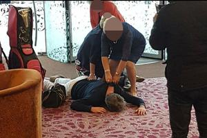 The photo shows Mike Nesbitt flat out on the lobby's carpet while one woman sits on his legs and another holds on to his collar