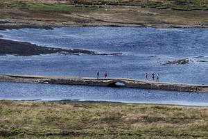 Members of the public walking on a normally submerged Roadway and Bridge in Spelga Dam in the Mourne Mountains