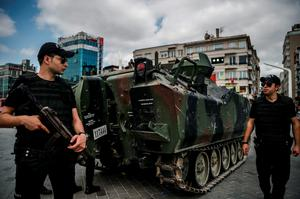 Turkish anti-riot police officers stand next to an armed vehicle at Taksim Square in Istanbul