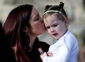 Michael McGibbon's wife Joanne kisses her daughter as the coffin is carried into the church
